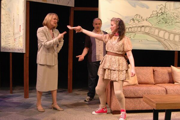 Aliza Moran, right, plays the character of Sylvia (a dog) and taunts Kate, played by Bonnie Kourvelas, as Greg, played by Tony Isbell, looks on in Sylvia at Theatre Memphis.