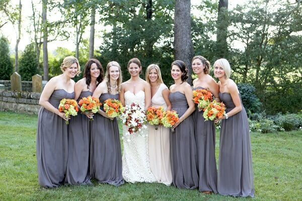 Caption:  By selecting a neutral palette of color for the bridesmaid dresses, their bouquets offer a gorgeous burst of color.   The bouquets, created by the Tulip Tree, are made of roses, hydrangeas, dahlias, and hypericum berries.  What a wonderful idea to have the maid of honor, the bride's sister, wear a gown that complimented the wedding dress.