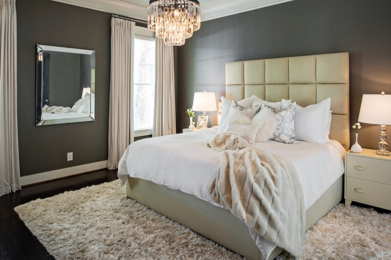 The master bedroom is uncluttered and beautiful. The headboard from Mitchell Gold and chandelier from FILLIN are both standout beauties against  this  FILL IN paint by Benjamin Moore.