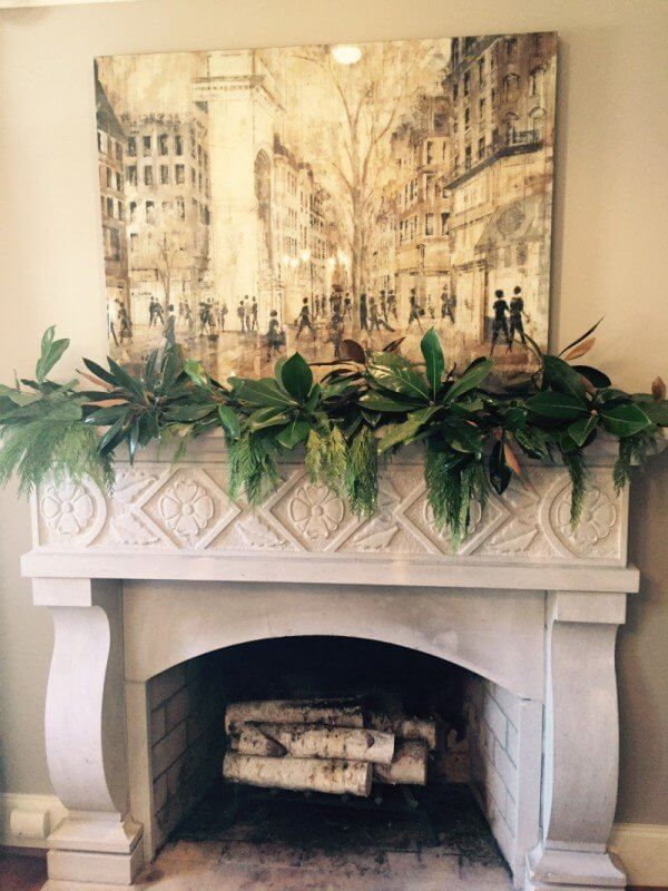 Lush greenery adds the perfect backdrop to this mantle featuring a Meredith Keith painting.