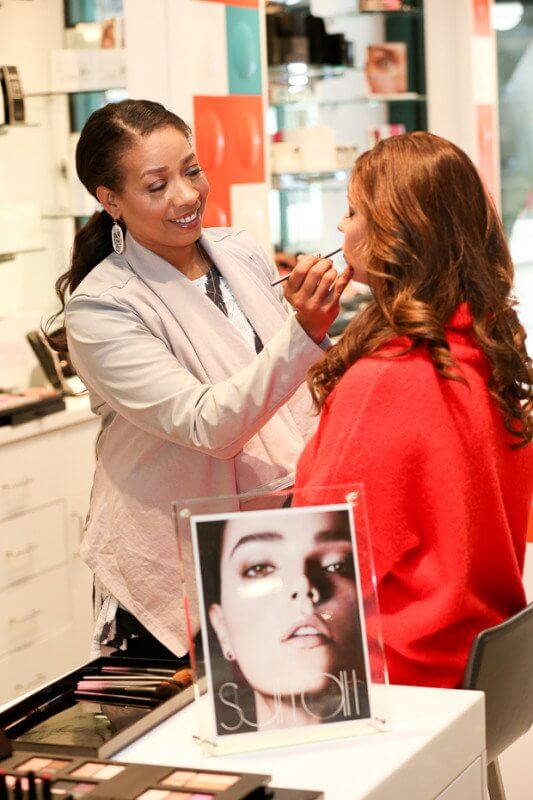 Nyssa Green touches up the lips of a lucky shopper. She loves the Troy Surratt line available at The Cosmetic Market Avalon.
