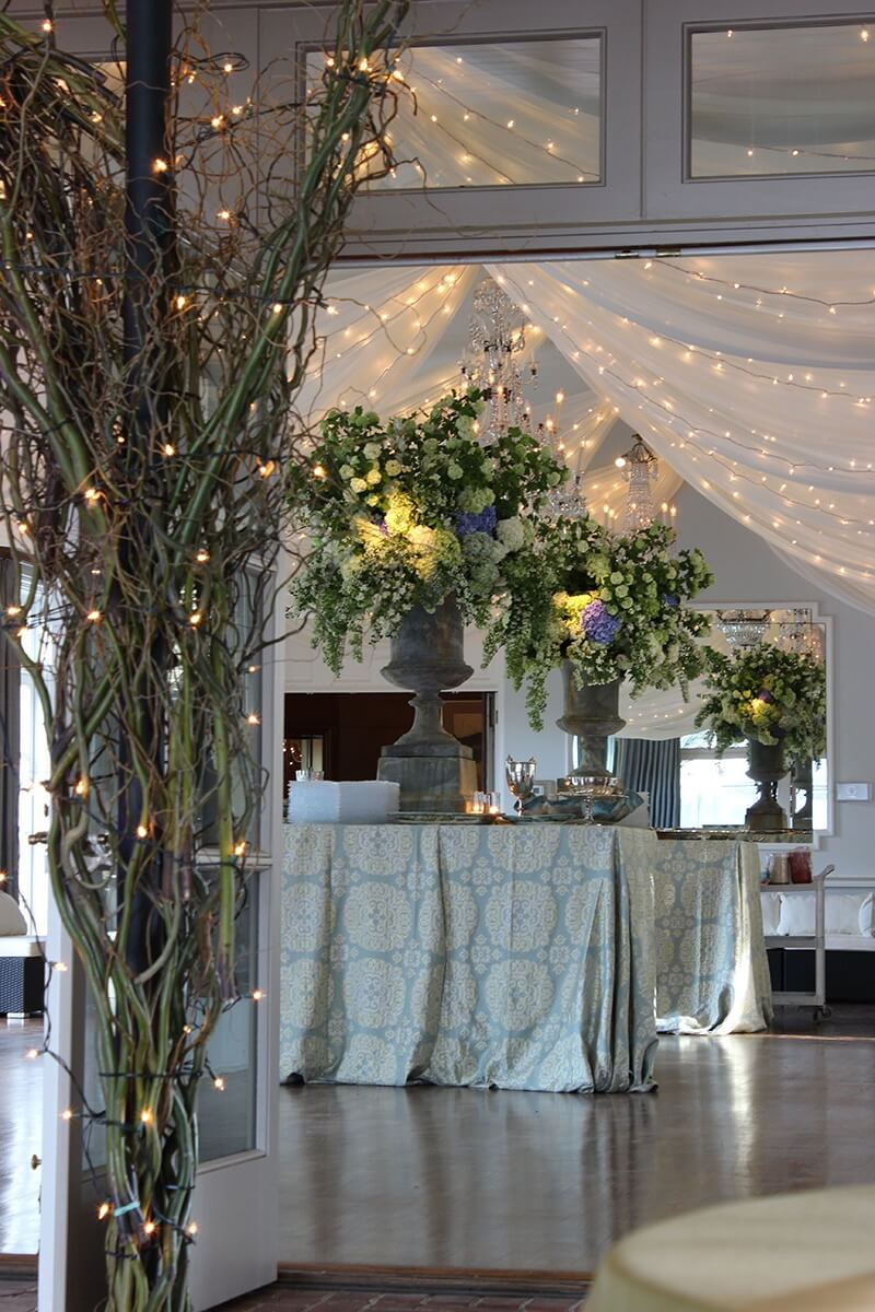 The draping of tulle and white lights such that the tent and ballroom were joined in seamless transition proved to be a mood-setting element created byt the Garden District.
