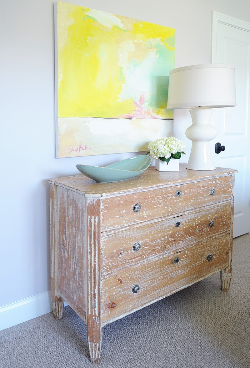 A Home by Chestnut Hall - In the girl's room, a bright painting by Chestnut Hall artist Hillary Butler hangs over the French-inspired, limed oak chest.
