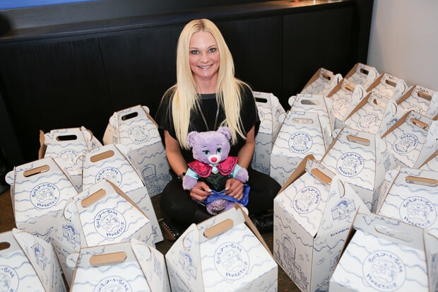 Stacey Weiss, co-founder of Bert's Big Adventure sits among boxes from one of BBA's corporate partners, Build-A-Bear Workshops,  who create custom plush pals for each child headed out on the trip.