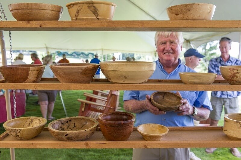 a woodworker at the annual, family-friendly Arti Gras festival on the Town Green, featuring wares from local artists and craftsmen