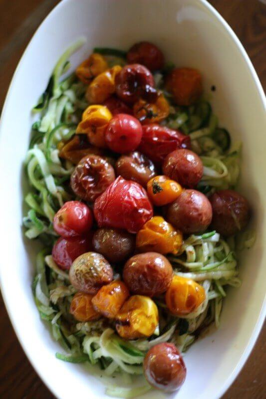 Zucchini noodles with roasted tomatoes in white bowl