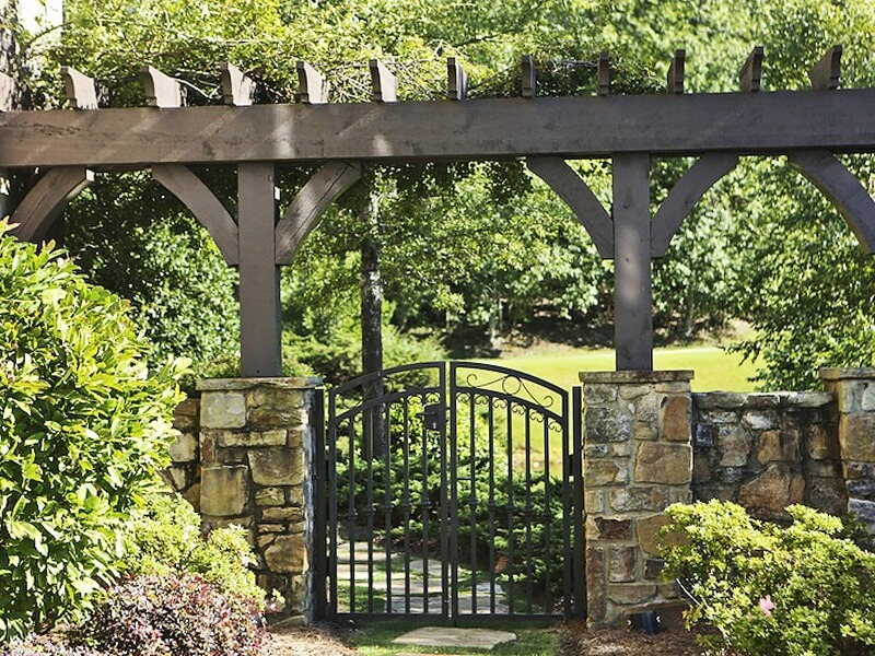 A picturesque stone wall and gate enclose the impressive outdoor spaces of this mountaintop home.