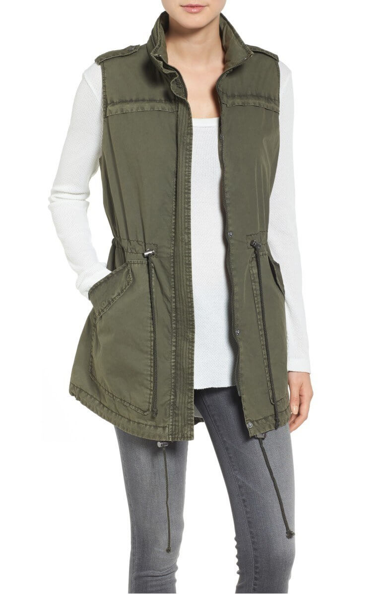 Here is an example of an olive green military-inspired vest that we love. The short sleeves and cinched waist are flattering, while the spacious pockets are useful and practical. Here, you can also see how long sleeves can work under a vest when paired with neutral, form-fitting bottoms. Find this vest for $58.90. Details here. Image: Nordstrom