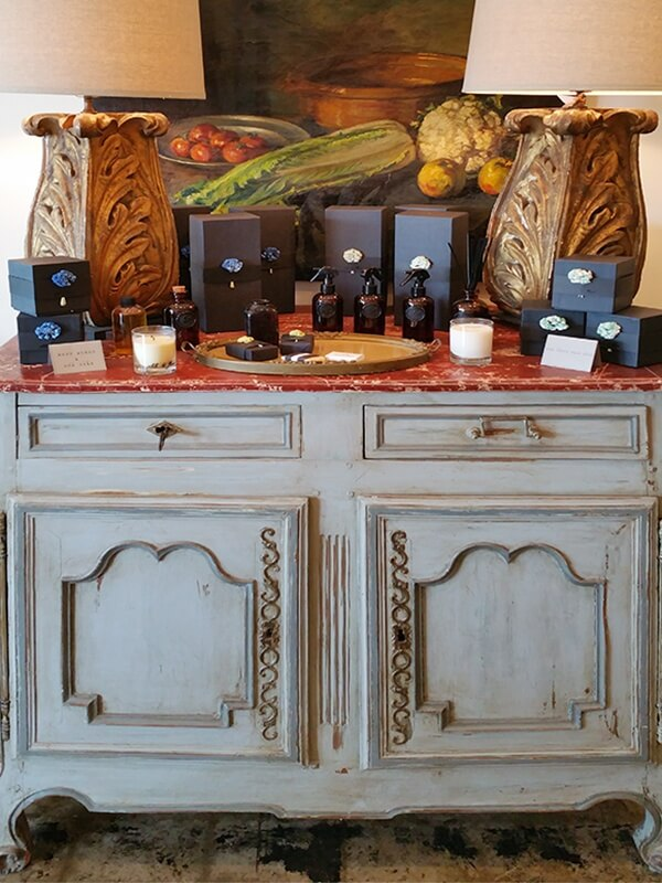 An antique sideboard display features a lovely still life, beautiful lamps, and soaps and candles.