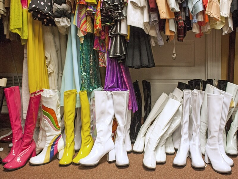 An impressive lineup of go-go boots rests under an array of psychedelic '60s wear.