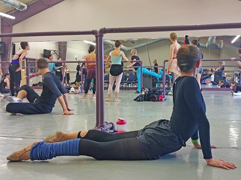 A dancer pauses mid-stretch to listen to the combination.