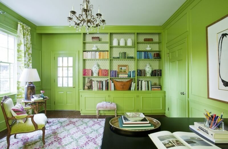 Lacquered walls the color of lime are a backdrop for green and white Quadrille drapery fabric and Quadrille fretwork wallpaper on the backs of the bookshelves.
