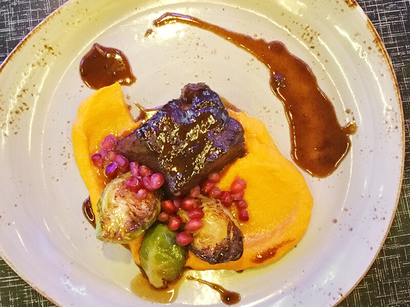 The red wine-braised beef short rib is served atop a butternut squash puree with charred Brussels sprouts and pomegranate seeds.