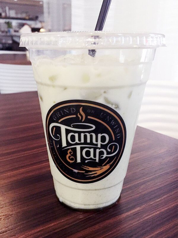An iced matcha latte is sweetened with honey.
