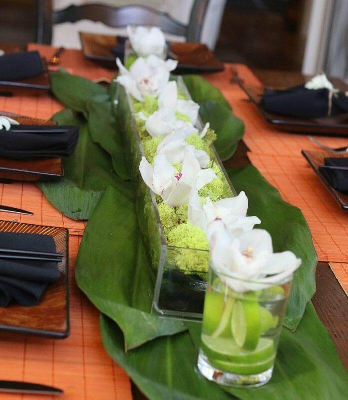 Orchids with river rocks centerpiece thai dinner party