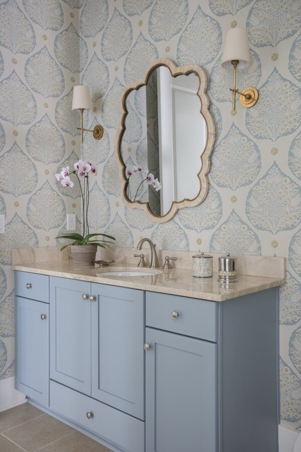 """The wallpaper was the inspiration for all of the design elements in this space, from the custom paint color on the vanity to the bone inlay mirror,"" says interior designer Lauren Leonard."