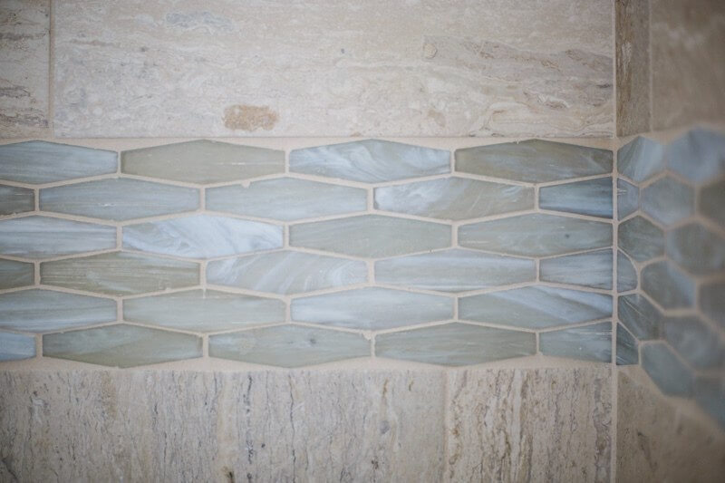 Glass tiles in different shapes were used throughout the bathroom, including this border in the shower.