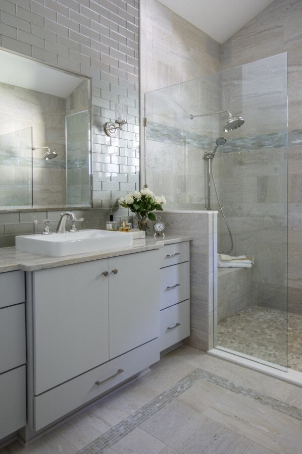 """""""The master bathroom has lovely, vaulted ceilings, so for a dramatic effect we ran the tile up to the ceiling,"""" says Leonard. The countertops are White Macaubus quartzite, which has the same beautiful green-gray veining that is found in the glass subway wall tile."""