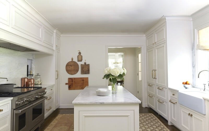 """Alabama white marble from Sylacauga is the crowning beauty of this kitchen. """"In addition to the countertops, we choose to do full height slabs of Alabama white marble for the backsplash with the pretty detail on each side of the window that has become one of our signature styles,"""" says Cyndy Cantley of Cantley & Company."""