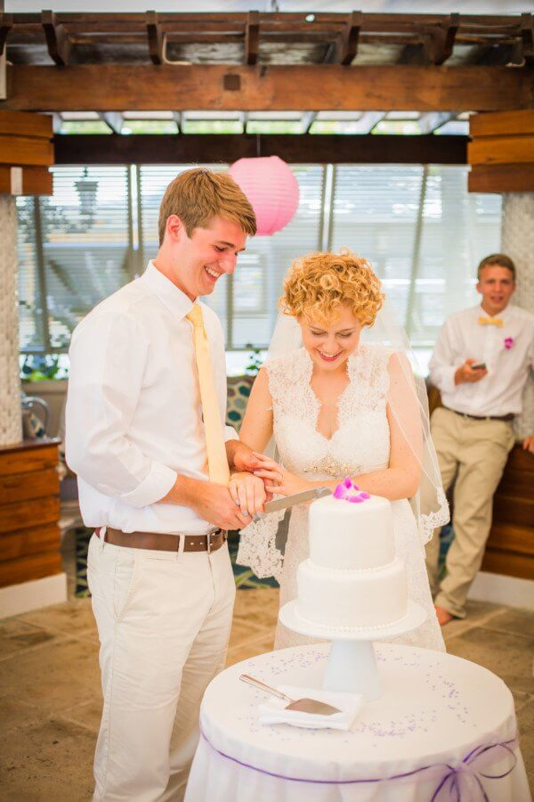 Kayla and Austin cut into their classic white cake topped with a single orchid, matching those in Kayla's bouquet.