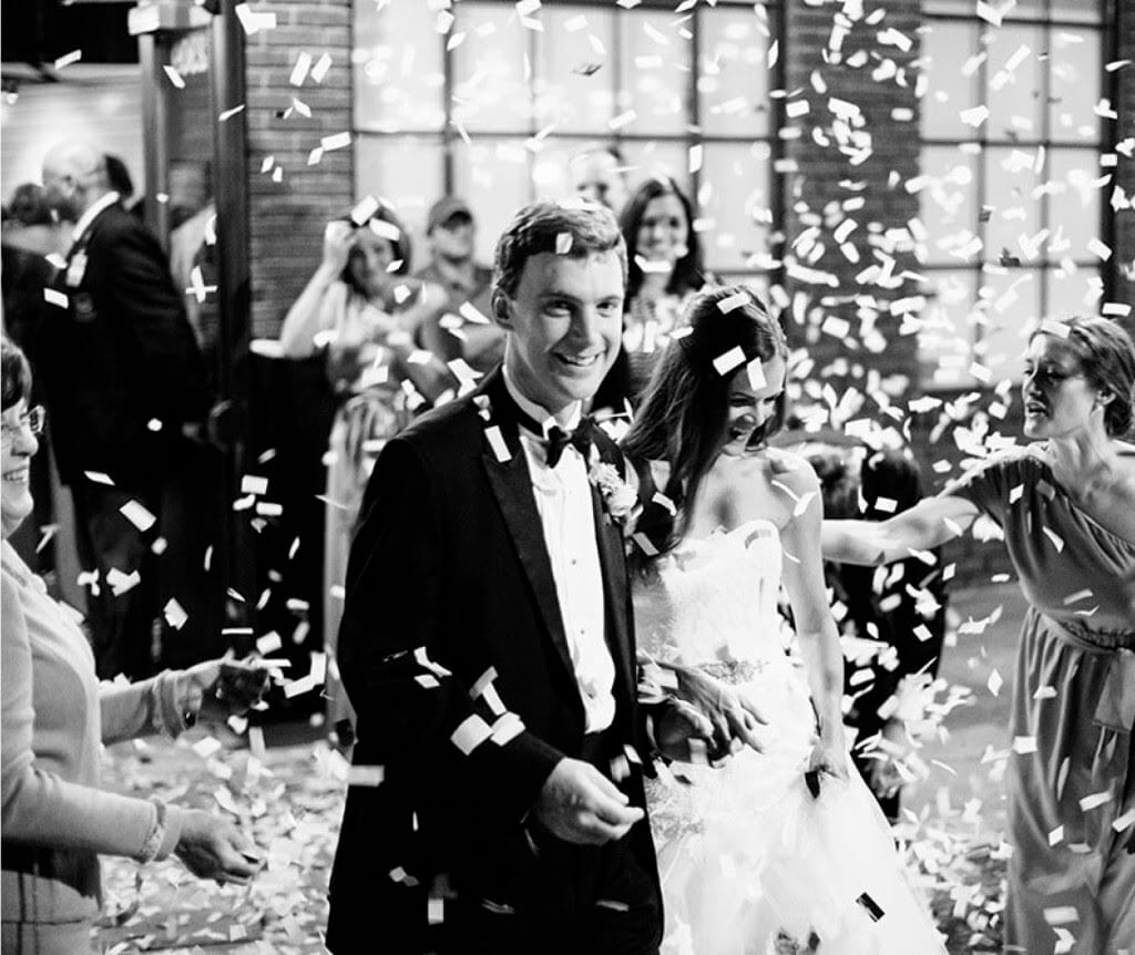 The happy couple exits under a shower of confetti, and the mother of the groom's boy is all smiles! Image: Kellen Jacobs Photography