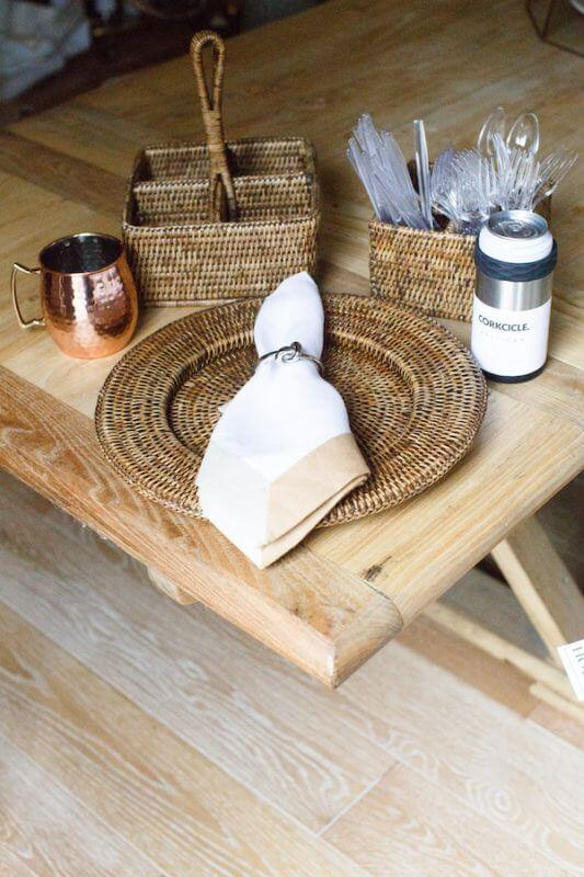 Rattan bamboo charger, $24; Moscow Mule cup, $18; rattan condiment holder, $34; rattan utensil holder, $34; custom napkin ring set, $48 and artisan Corksicle, $19.99, from House.