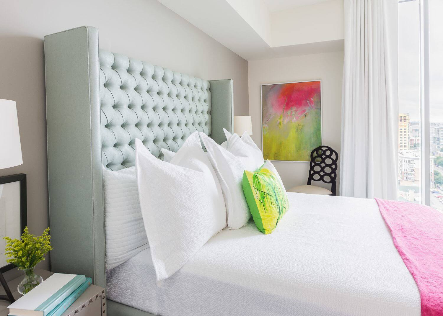 The artwork on the bedroom's wall ties in the colors of the headboard, pillow and throw. ©Alyssa Rosenheck Photography