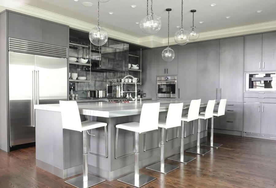 Glazed oak cabinets in a warm gray hide a lot of the workings of this Atlanta kitchen, allowing the countertops to stay uncluttered. Kitchen designer Kelly Carlisle also designed a clever backsplash with oxidized metal tiles to reflect light.