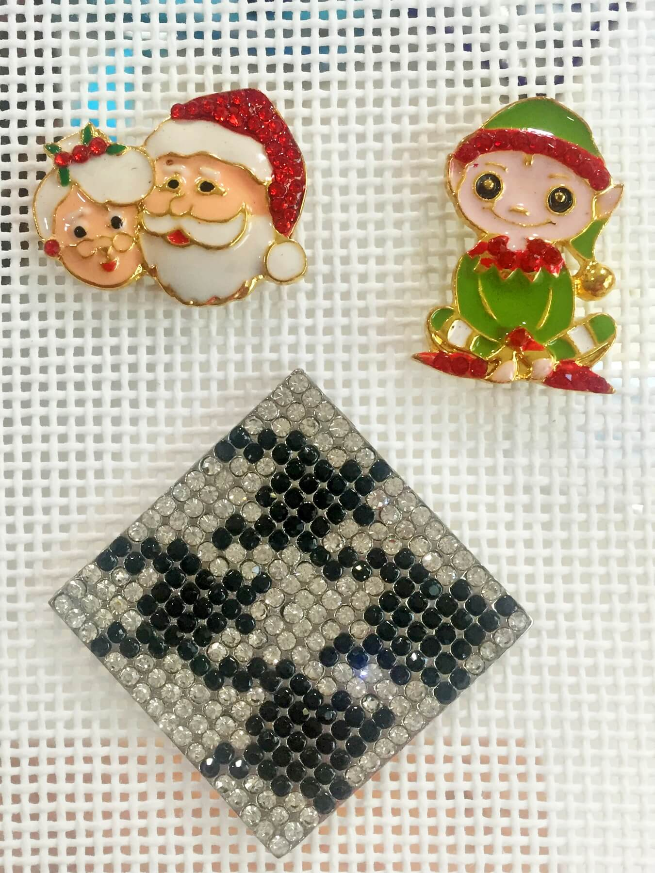 Santa and Mrs. Claus magnet, $16; Santa's elf magnet, $16; and houndstooth square magnet, $23, at Needleworks LLC