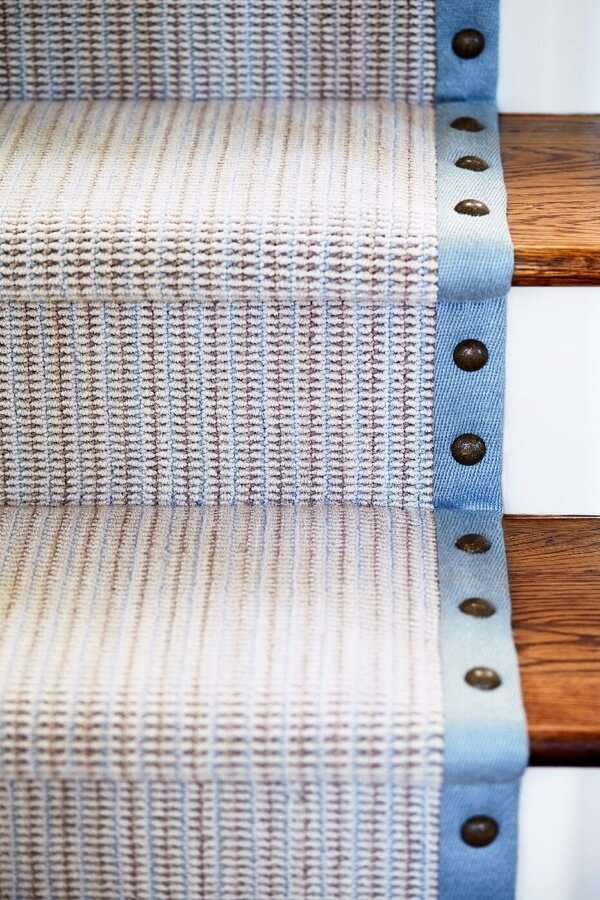 A stair runner with a nail-head border brings in texture, warm metals and a soft blue accent to the space.