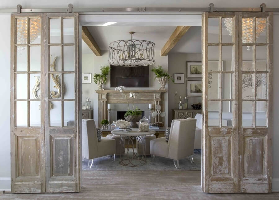 """I ran across a pair of old French doors that were fabulous and I knew immediately we had to incorporate into the design somewhere,"" says Carol.  ""We decided to have them hung on a stainless sliding bar to frame out the living room."" This antique mantel originally was housed in the Yale library back in the 1900s."