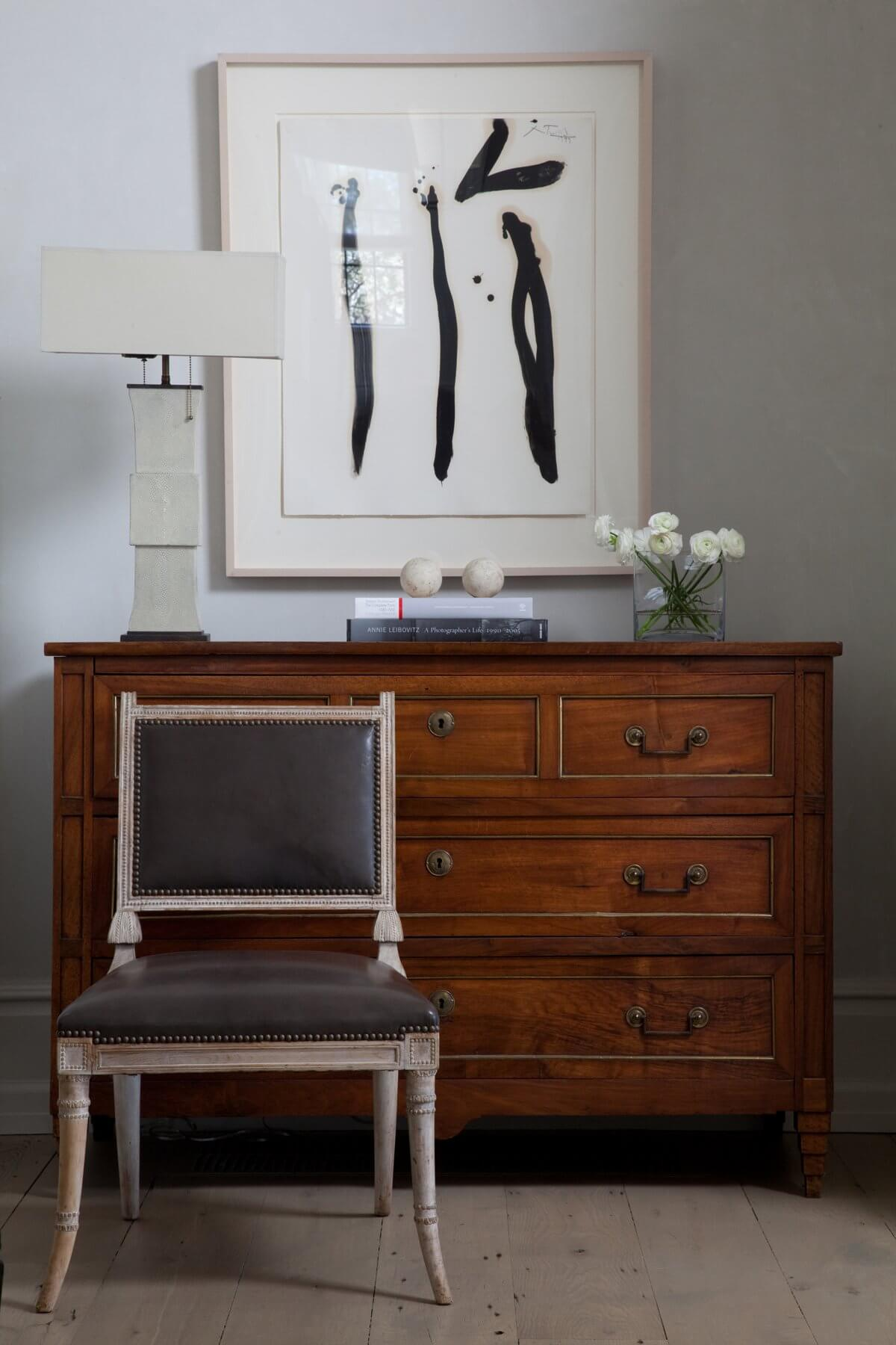 An antique Italian chest with Ziggurat legs is flanked by a 19th Century English regency chair in the entry of the home. Image: Miller Mobley