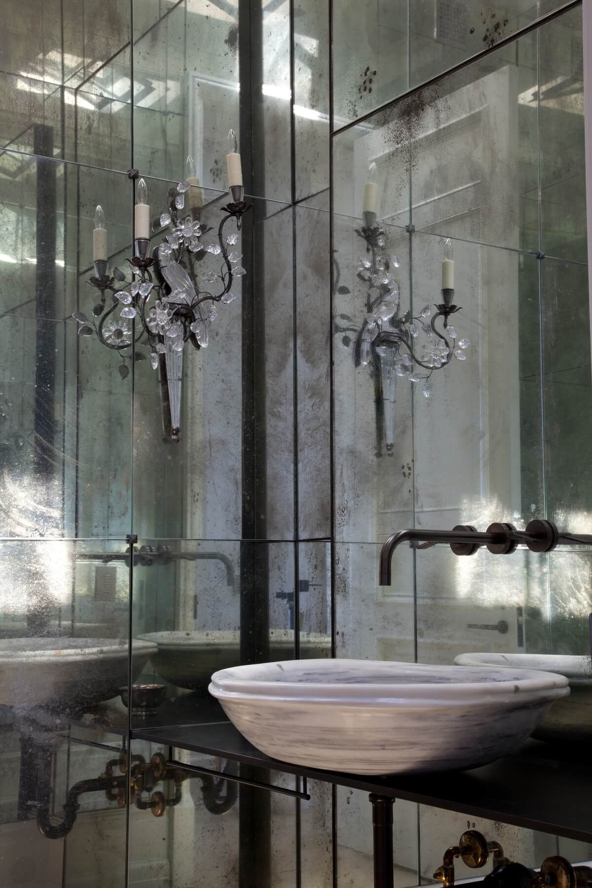 This striking powder room with its antique mirrored walls, pair of iron and crystal bird sconces and antique Turkish stone sink is truly one of a kind. Image: Miller Mobley