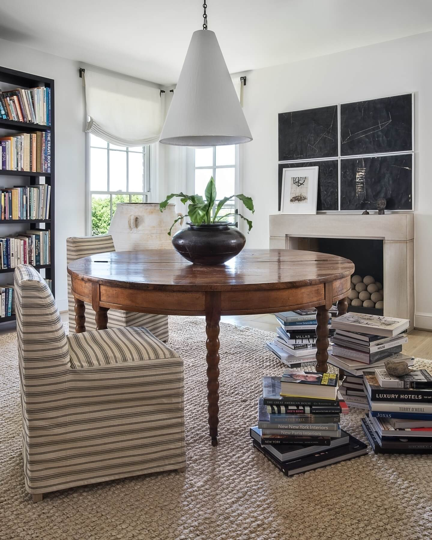 The library's 19th Century French drop-leaf table is topped with a plaster cone hanging light by Rose Uniacke. Image: Peter Vitale