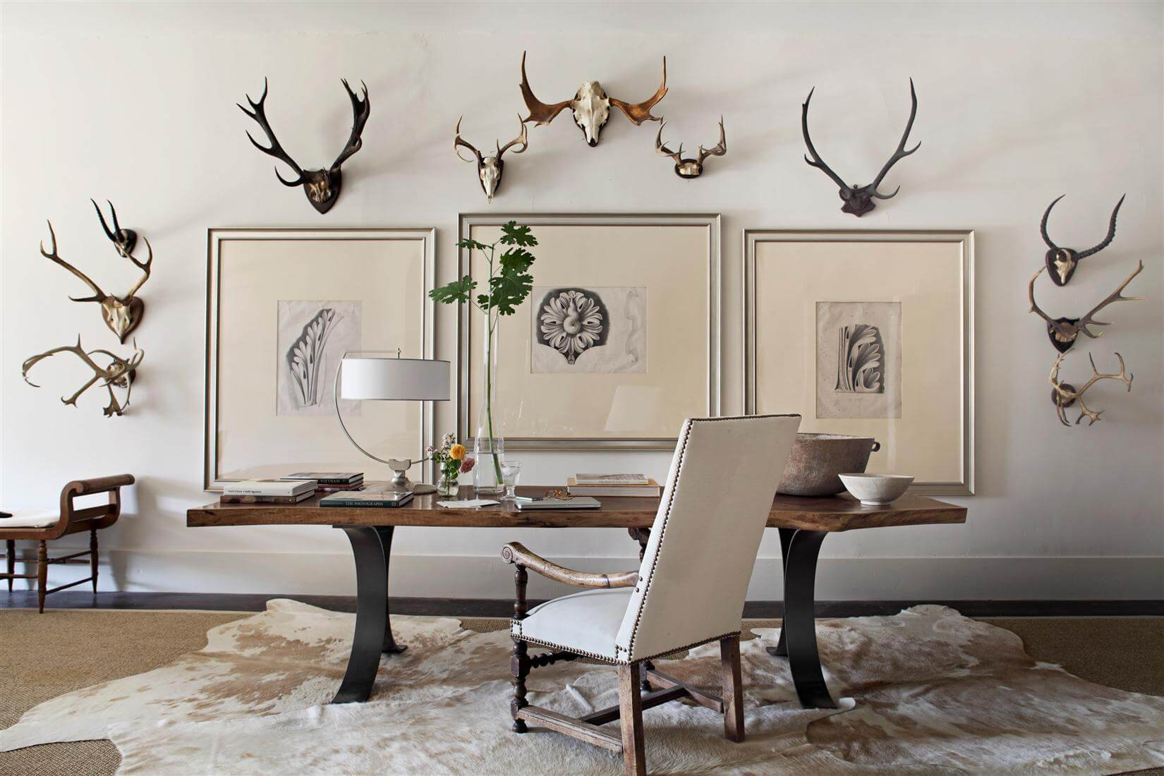The client's own collection of vintage European antlers gets its day in the sun beside antique prints of Greek Revival plaster designs in this upstairs hallway vignette, where an 18th Century Louis XIV-style armchair flanks a custom walnut table by Michael Morrow. Image: William Abranowicz