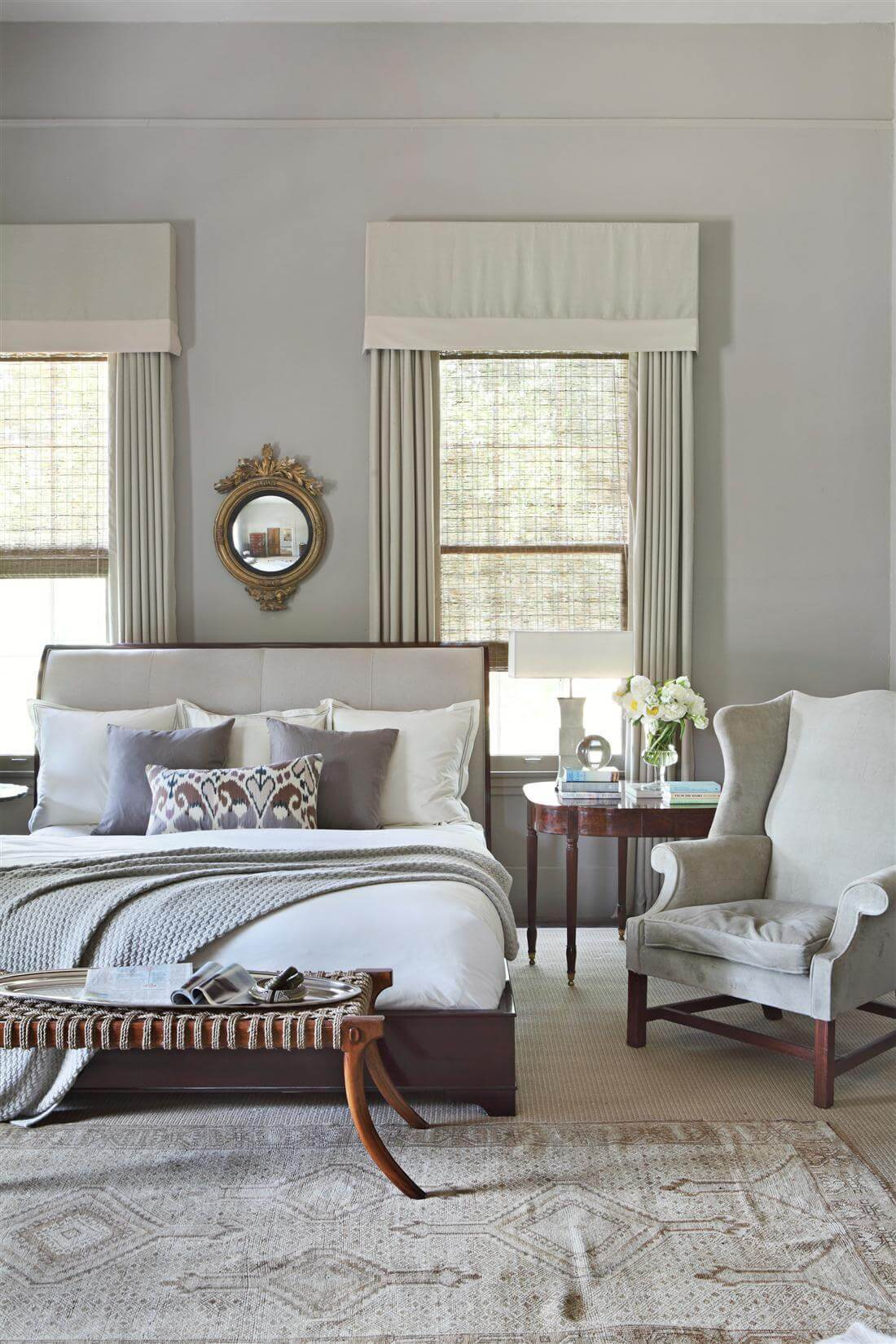 The master bedroom includes an upholstered sleigh bed, antique Georgian wing chair, saber leg ottoman by Formations, a bullseye mirror and an antique rug from Paige Albright Orientals. Image William Abranowicz