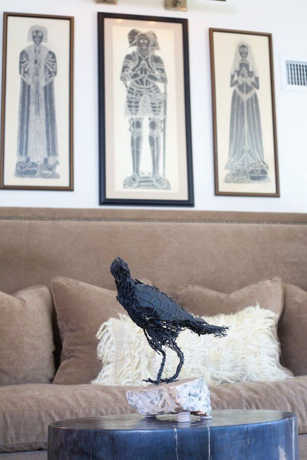 A black crow made of chicken wire and rubber tire by artist Randy Gachet is perched atop a petrified wood stump in front of a banquet, above which three vintage brass rubbings lend a stately, Old World air.