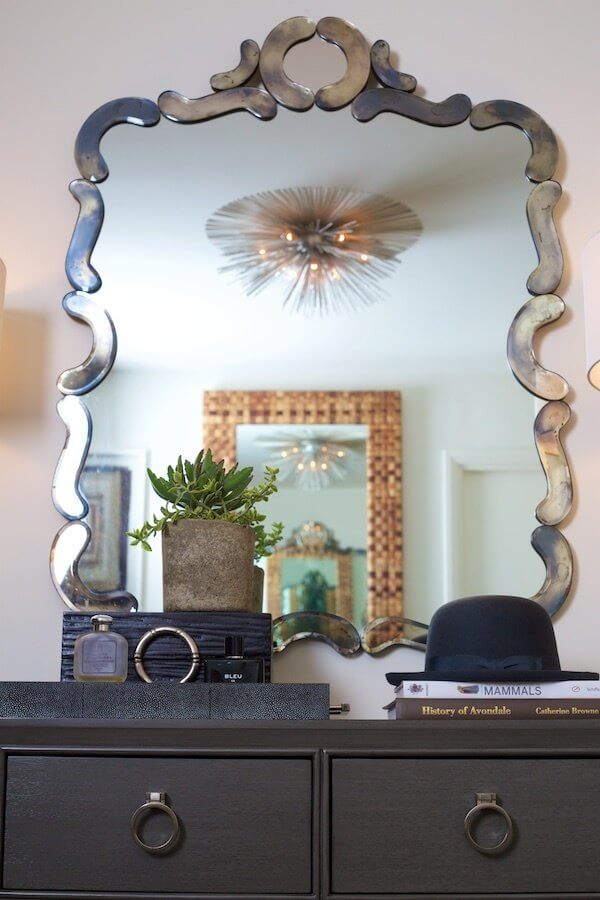 The couple inherited this striking mirror from a friend. The dresser by Vanguard Furniture anchors a smart arrangement of coffee table books, cologne, and a custom beaver hat by Orlando Palacios for Worth & Worth.