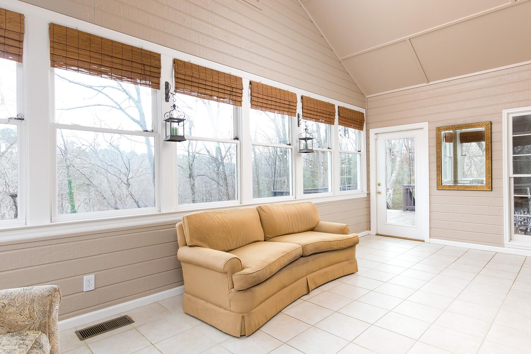 The wall of windows and pitched ceiling in this gorgeous sunroom are to-die-for!