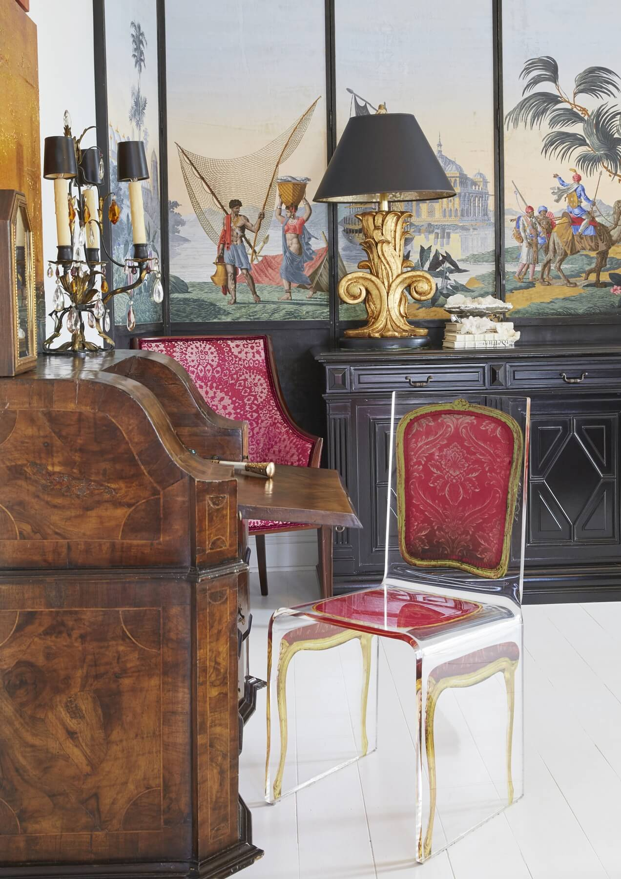 Em found this ghost chair with the image of a pink-upholstered French chair on 1st dibs, and was so delighted with it that she had to have it. In the background, another longtime piece she's always treasured is a 12-foot long French sideboard cabinet, which was once stained brown wood that she updated with glossy black paint.