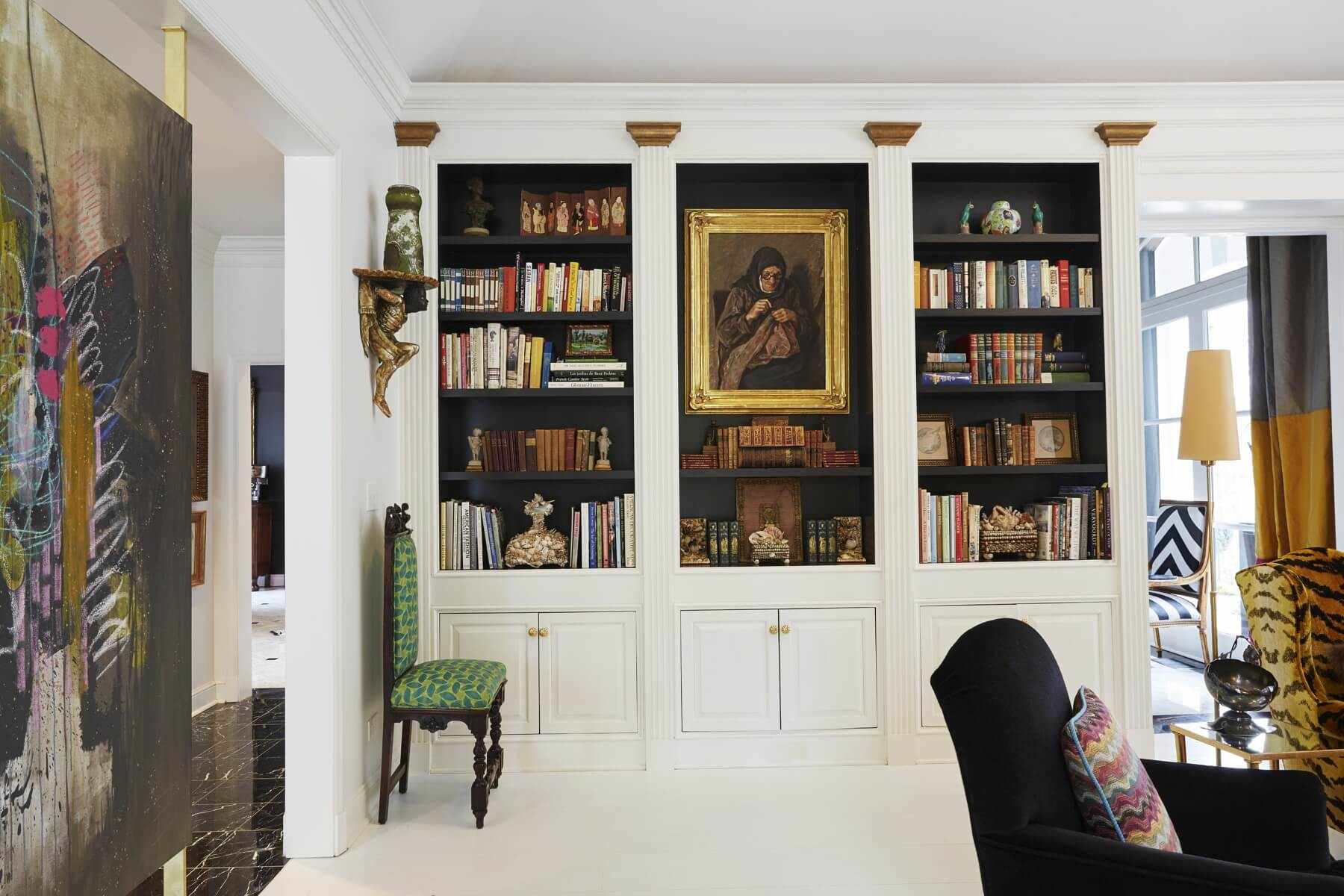 "Em repainted the built-in shelves in black with white façades. She reupholstered the pair of carved Spanish chairs in a Fortuny fabric purchased on the couple's 40th Anniversary trip to Venice. The painting at left is by Em herself and is entitled ""Free Gift of Grace."""