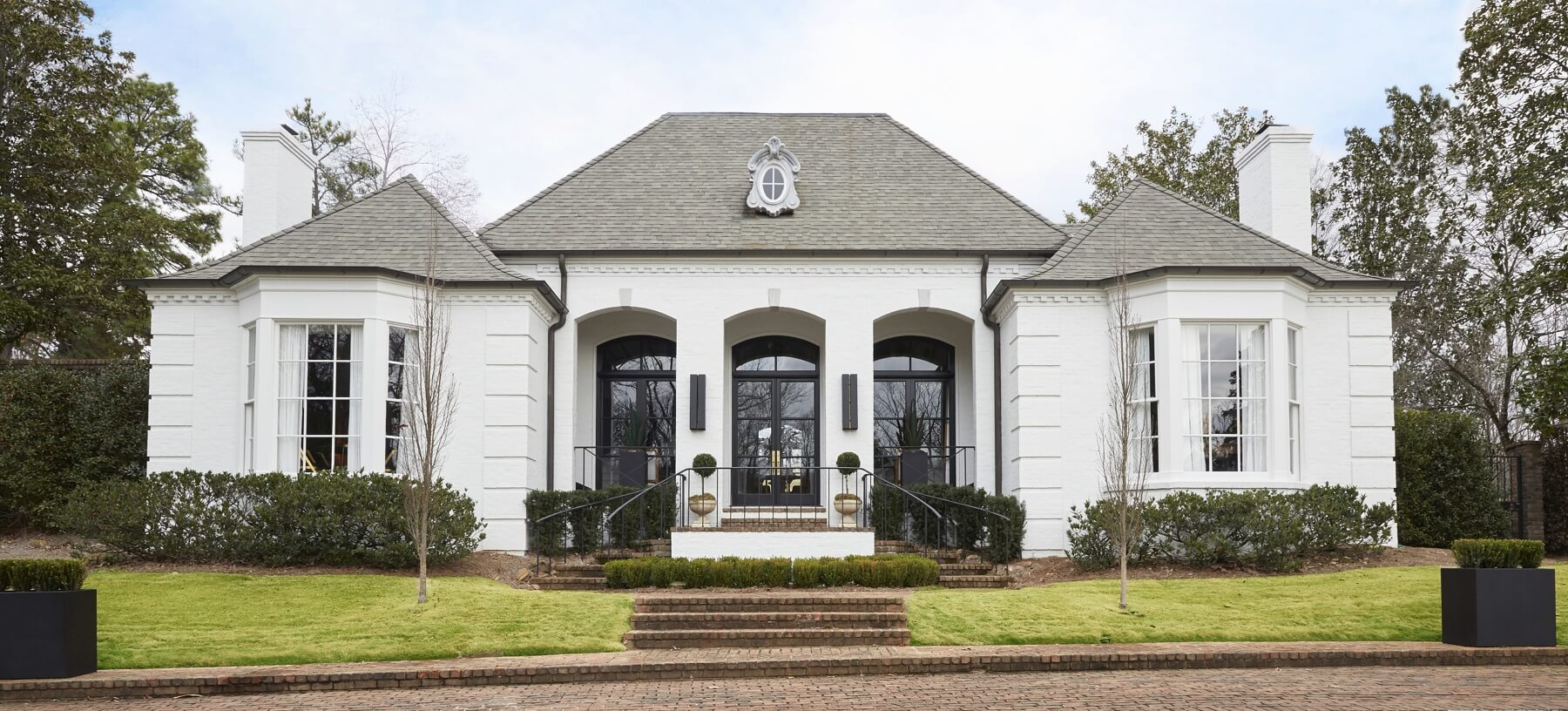 Em worked with Clarke Bohorfoush to streamline the landscaping and she painted the exterior white, in keeping with her original vision. Removing the color and overgrown greenery accentuated the facade's clean architectural lines and added dramatic emphasis to the three arched entryways.
