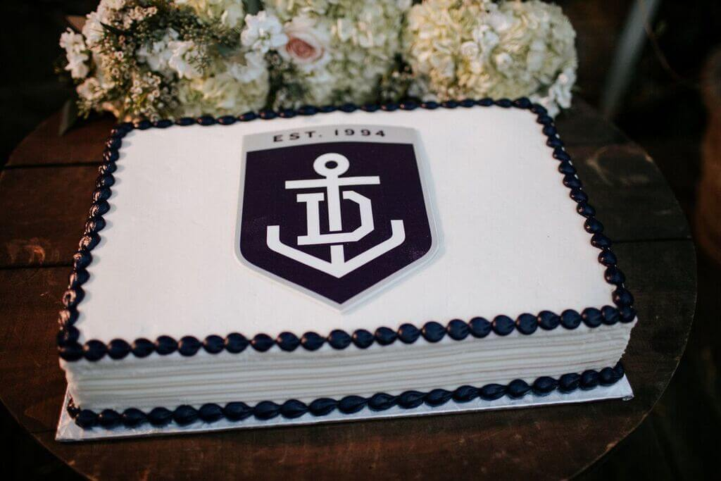 The grooms cake was a tiramisu cake with cream cheese icing and decorated with purple and white, the colors of Andrew's favorite football team- the Fremantle Dockers.