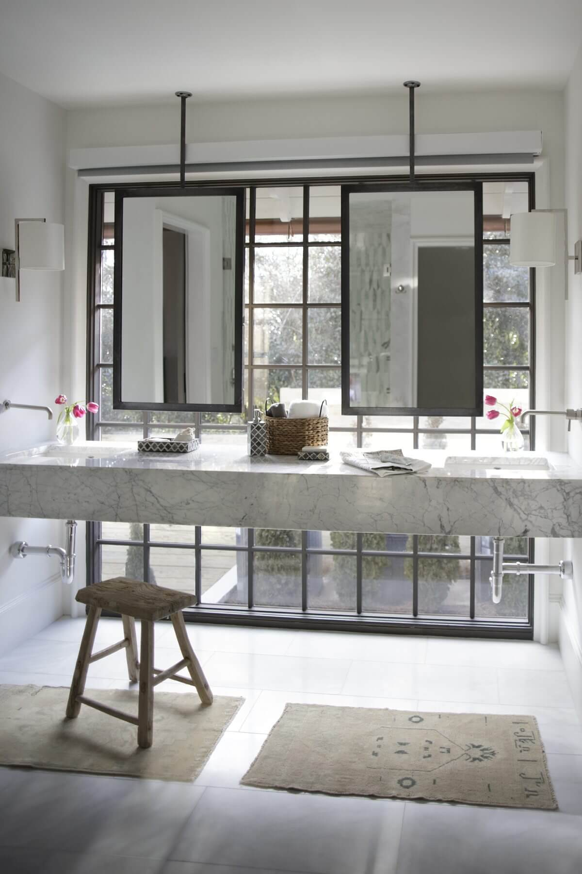 This gorgeous his-and-hers bathroom features natural light, marble, chic hardware and suspended mirrors.