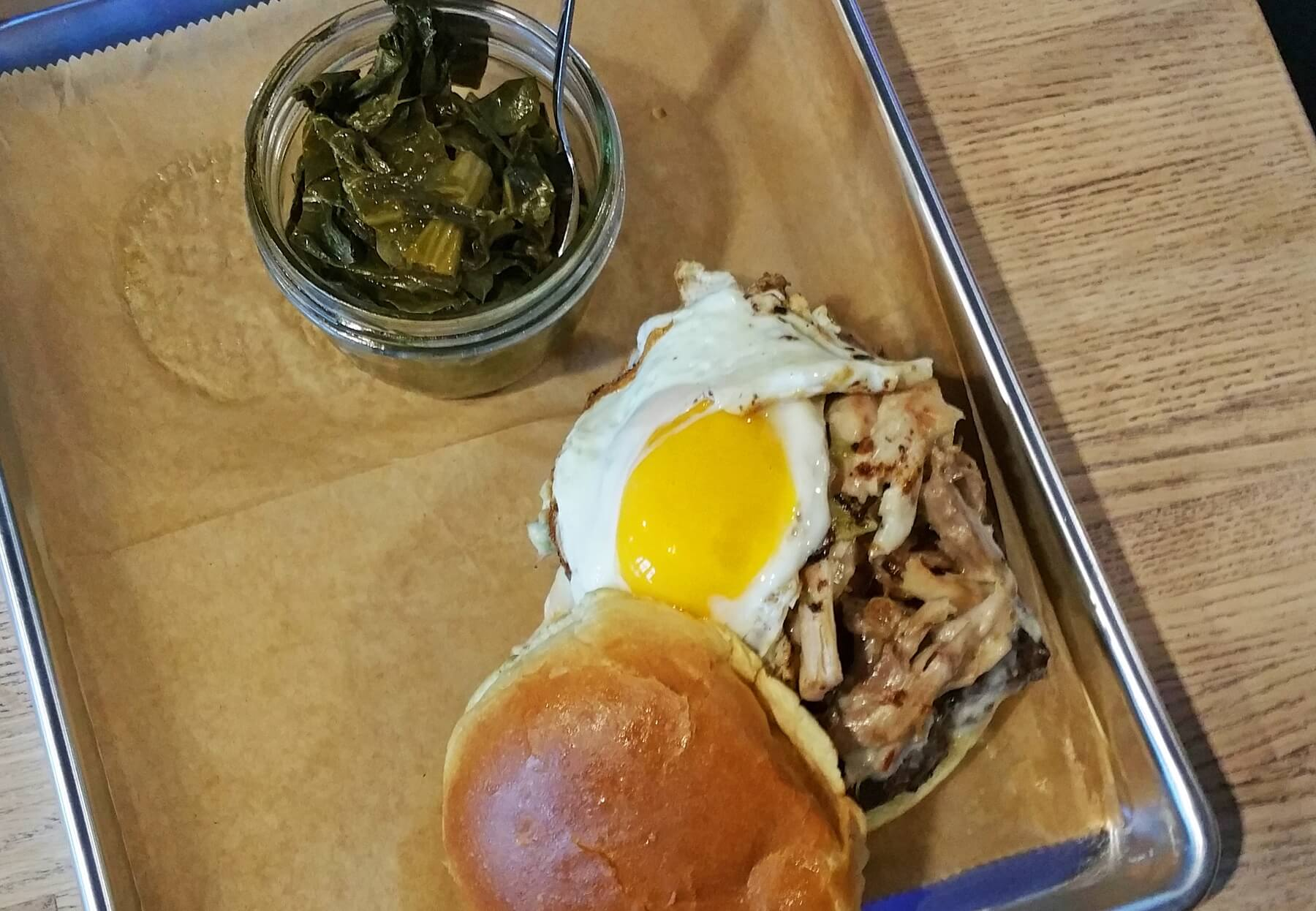 """The Farm"" burger features a short rib blend patty on a brioche bun with a smear of smoky mayo, topped with pork belly, duck confit and smoked turkey, drizzled in green chile queso,topped with a sunny-side-up egg and sprinkled with cracklins."