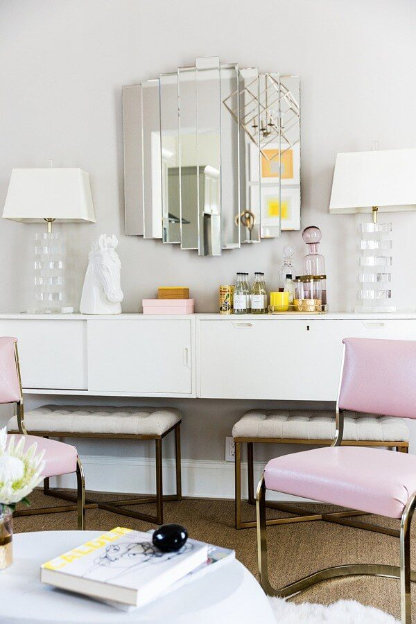 Bethany brought created a bar and ingenious storage with this floating cabinet. Lucite lamps with vintage seating and mirror make an elegant statement with a light touch.