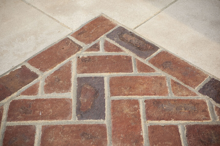 Even a transition from drive to walk can be elegant with the right materials. This design features Indiana limestone and brick in a running bond and herringbone pattern.