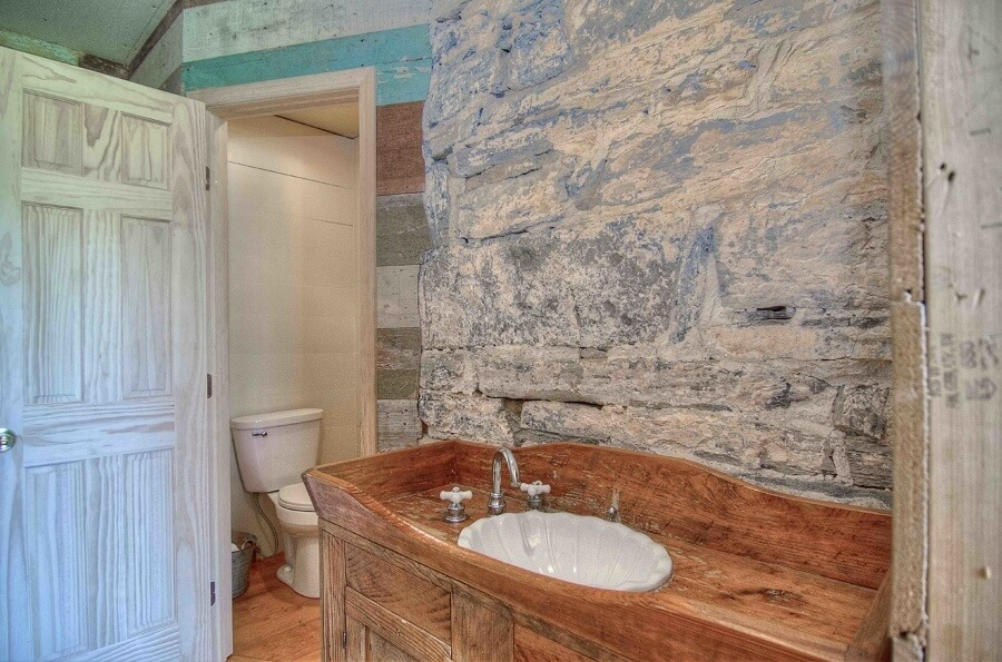 A rustic stone wall distinguishes this small bathroom — a concession to modernity added by the homeowners.