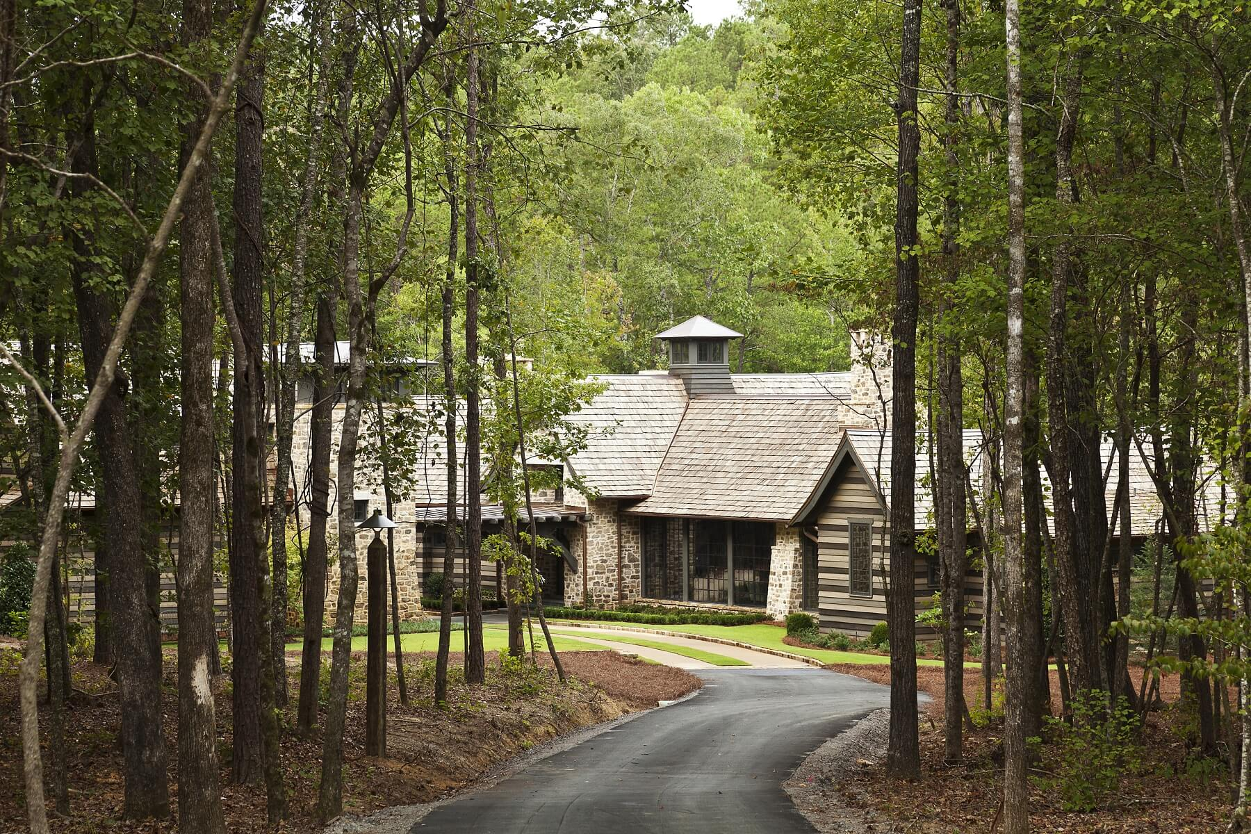 A long driveway winds toward the home, which is tucked among the trees.