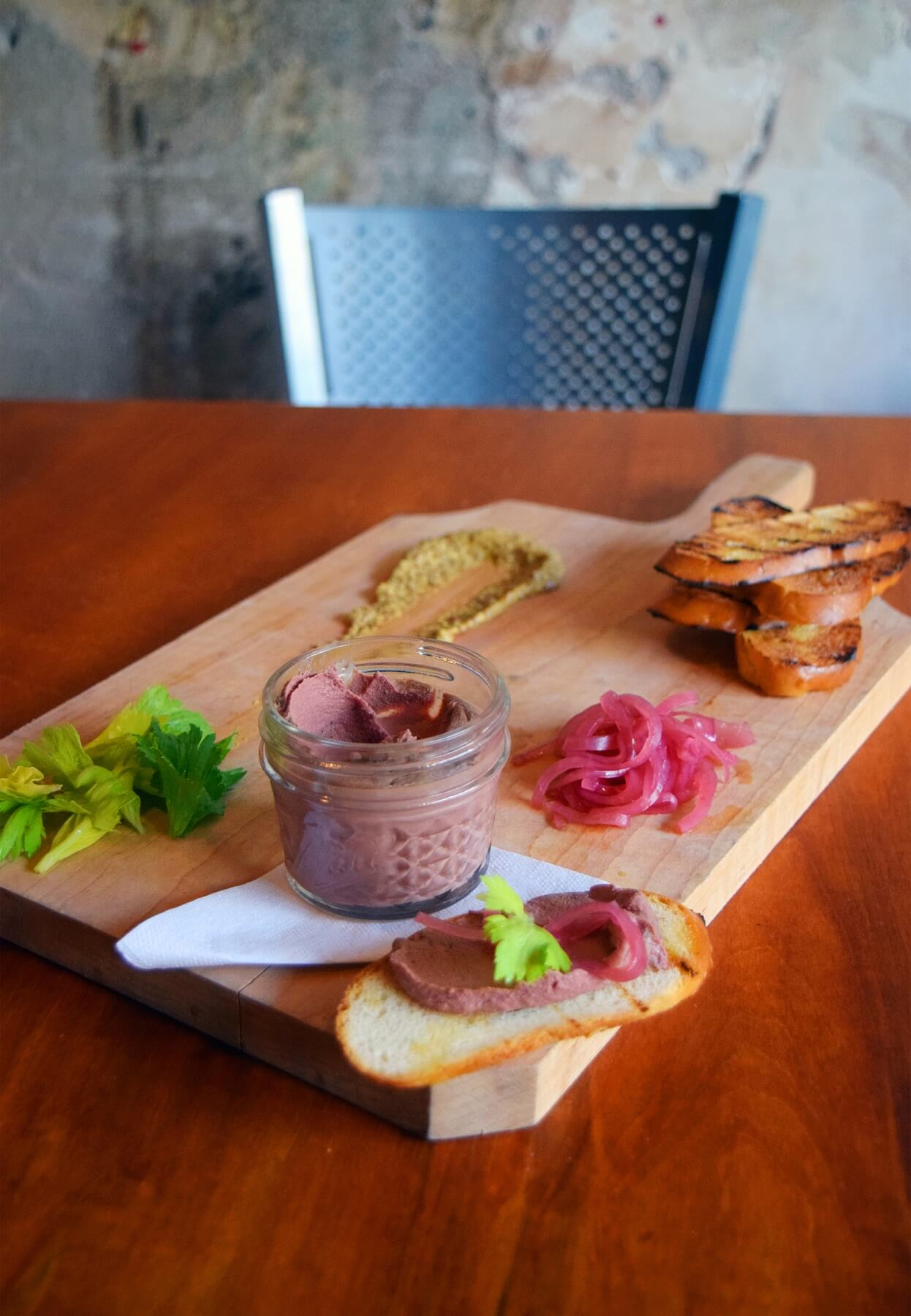Build your own crostini! House-made chicken liver mousse is served with grainy mustard, pickled red onion, celery leaves and grilled bread.